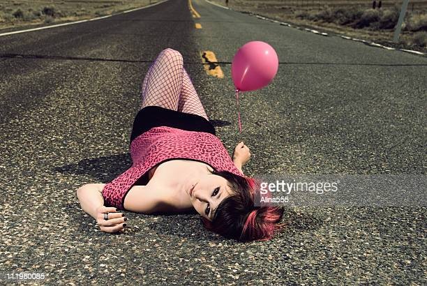 Young woman with is laying on the road holding balloon