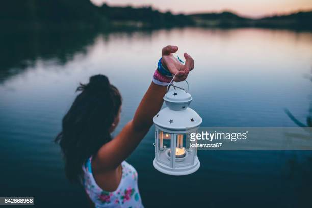 young woman with lantern exploring in nature
