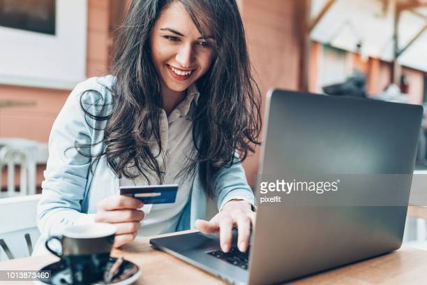 young woman with laptop and credit card in cafe - credit card purchase stock pictures, royalty-free photos & images