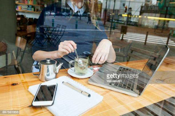 Young woman with laptop and cup of tea in a cafe, partial view