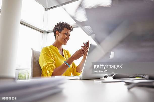 Young woman with laptop and smartphone in office