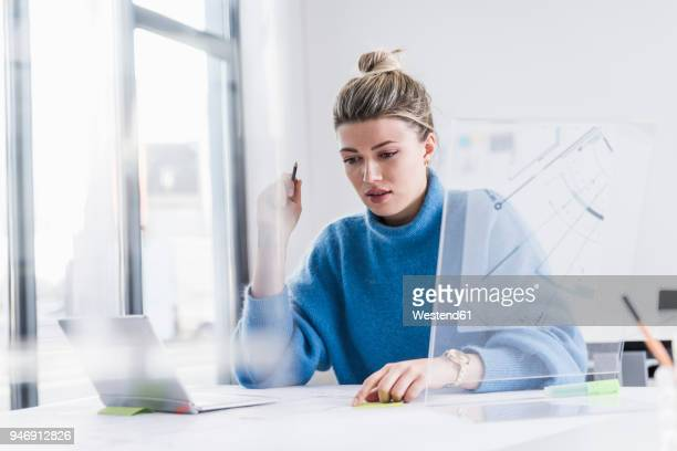 young woman with laptop and transparent design working on plan at desk in office - concentration stock pictures, royalty-free photos & images