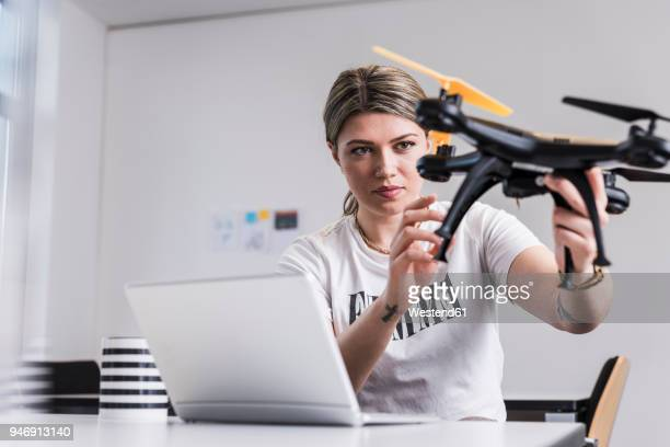 young woman with laptop at desk holding drone - drone photos et images de collection
