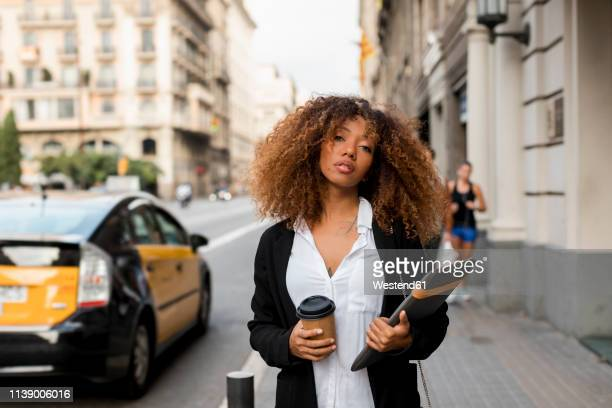 young woman with laptop bag and coffee to go in the city, missing the taxi - ongeduldig stockfoto's en -beelden