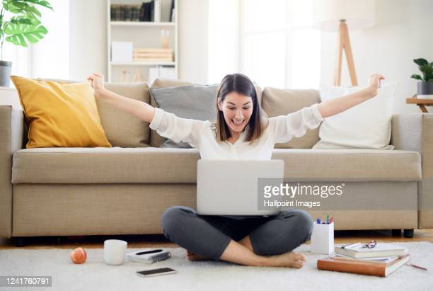 young woman with laptop expressing excitement in home office, quarantine concept. - success stock pictures, royalty-free photos & images