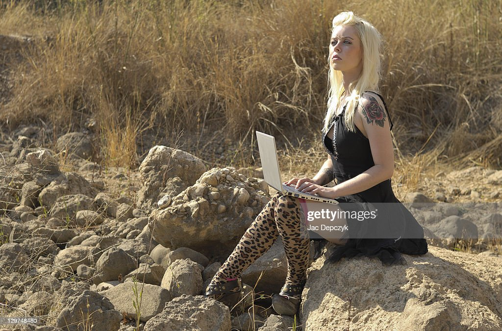 Young woman with laptop in dry riverbed : Stock Photo