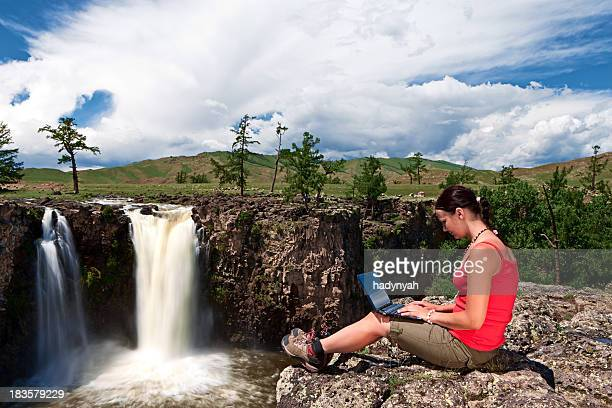 Young woman with laptop on rock