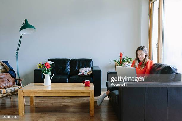 Young woman with laptop relaxing on the couch in her living room