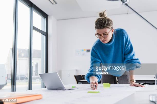 young woman with laptop working on plan at desk in office - bend over woman stock pictures, royalty-free photos & images