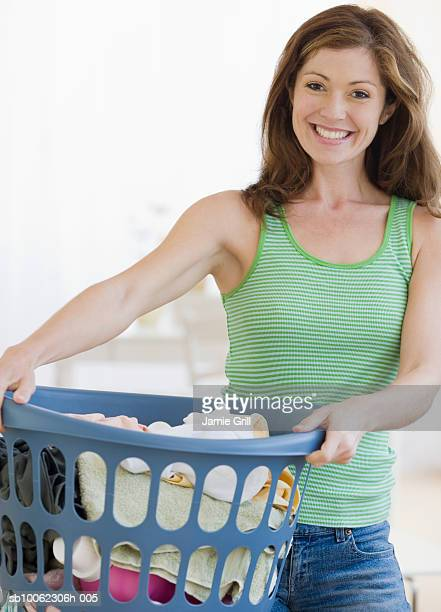 Young woman with laundry basket, smiling