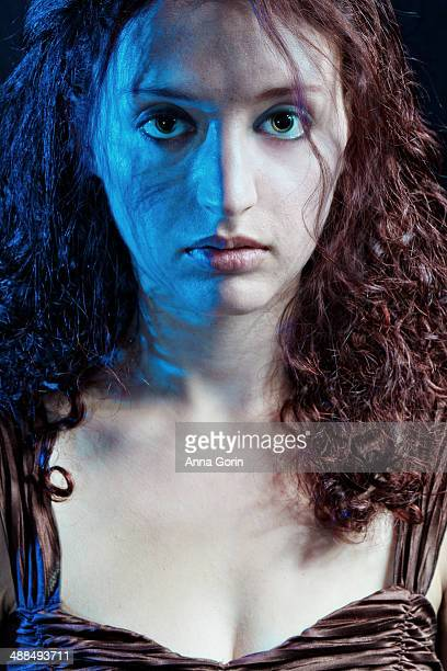 young woman with left side lit by blue light - gel effect lighting stock photos and pictures