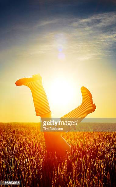 young woman with legs in the air at sunset. - appearance stock pictures, royalty-free photos & images