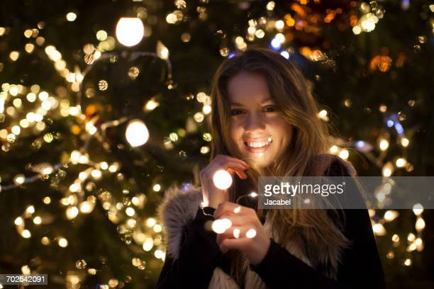 young woman with lights in her hand, tree in background - funky foto e immagini stock