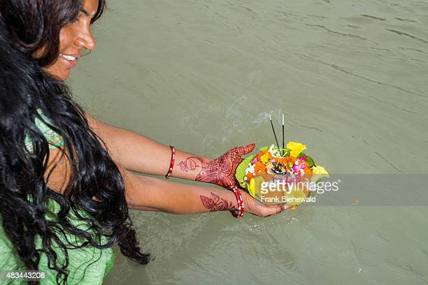 RISHIKESH UTTARAKHAND INDIA A young woman with long black hair henna painted hands and a green dress is holding a deepak a flower offering at the...