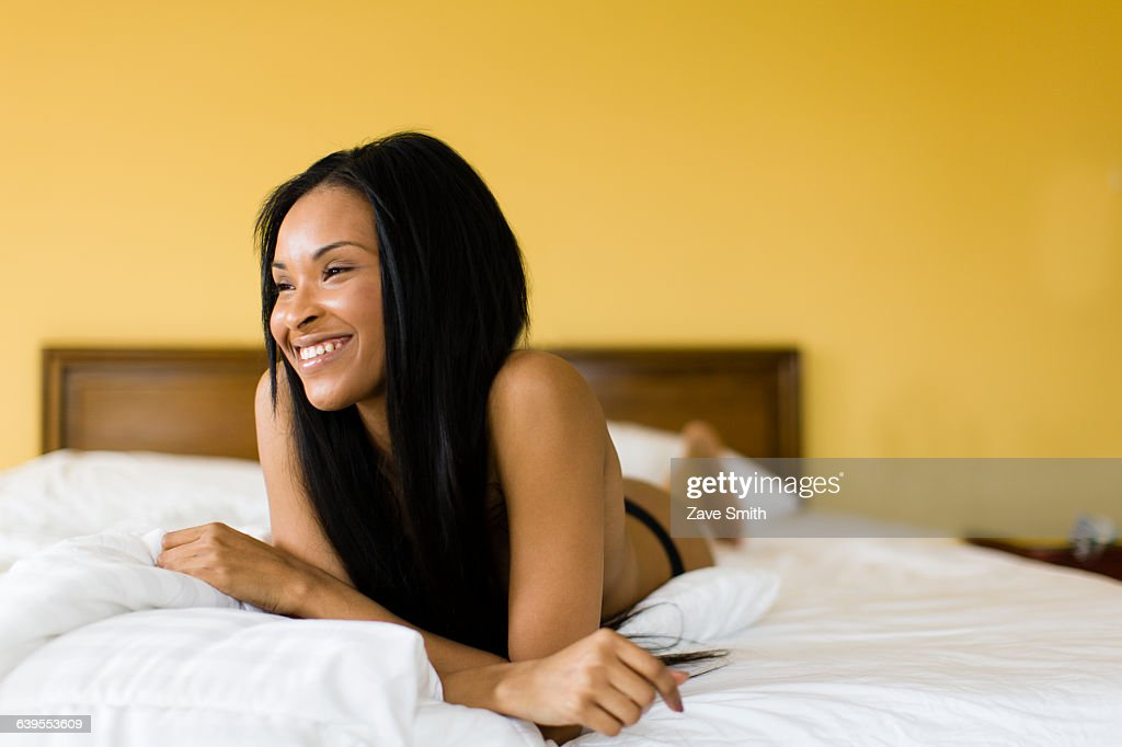 Young woman with long black hair wearing knickers lying on bed : Stock-Foto
