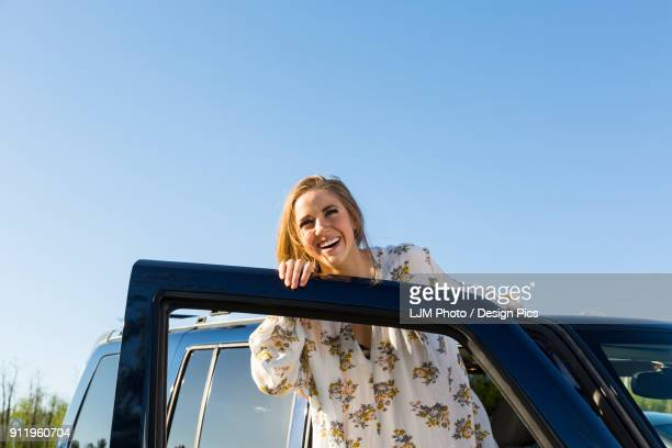 Young woman with long blond hair posing for the camera at the open door of a vehicle