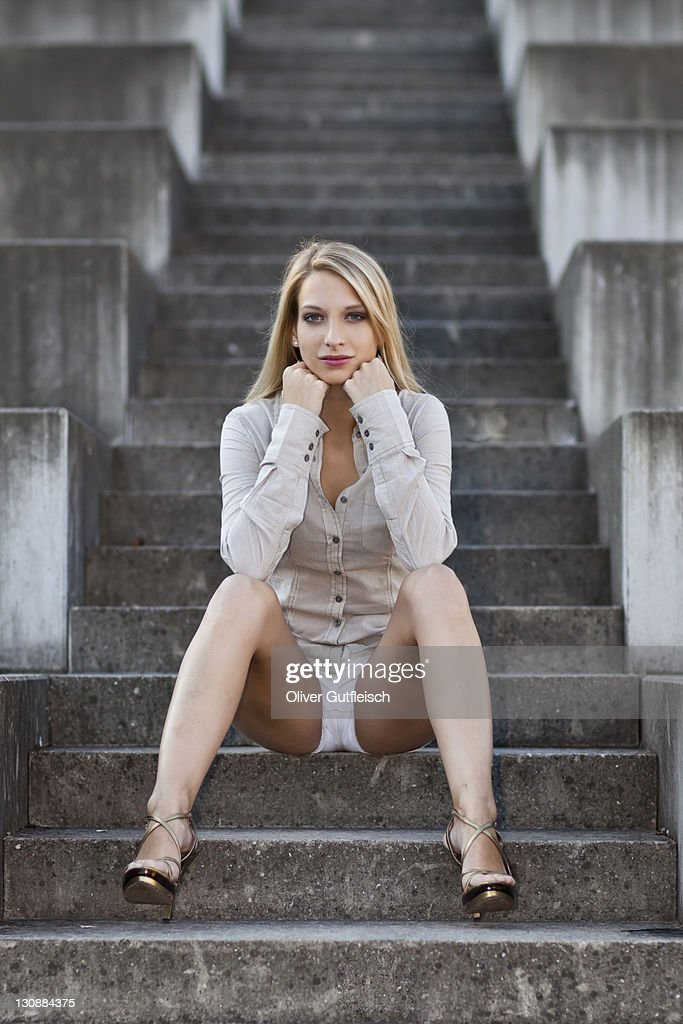 Young woman with long blond hair wearing a grey shirt, white shorts and high heels sitting on stone stairs : Stock Photo