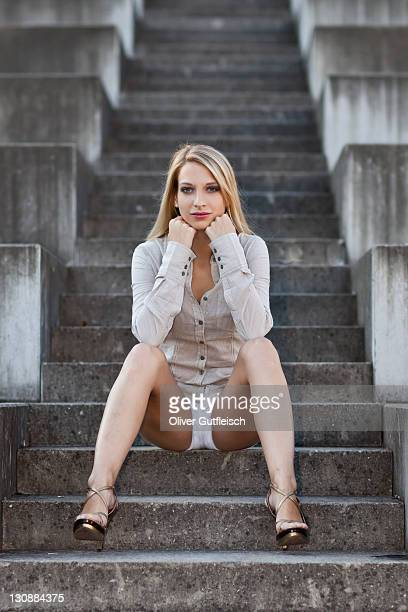 young woman with long blond hair wearing a grey shirt, white shorts and high heels sitting on stone stairs - queimadura pele imagens e fotografias de stock