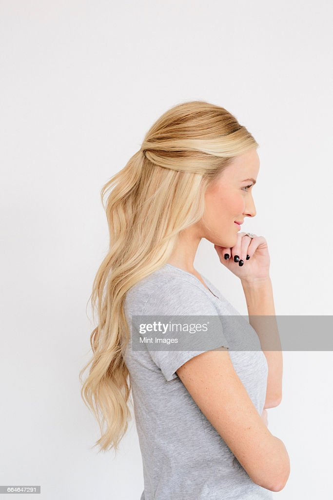 A young woman with long blond wavy hair. Side view. : Stock Photo