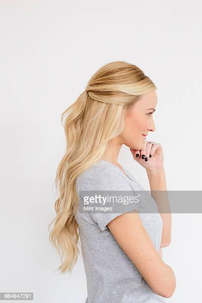 A young woman with long blond wavy hair. Side view.
