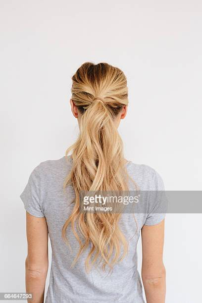 A young woman with long blond wavy hair tied in a ponytail. Back view.