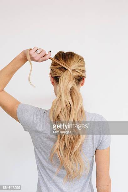 A young woman with long blond wavy hair. Tying a ponytail. Back view.