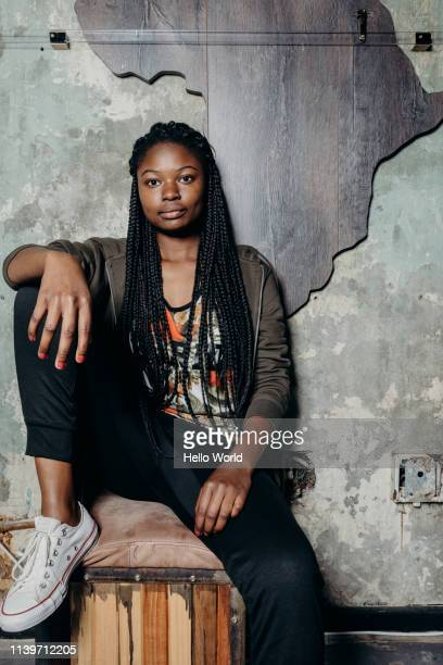 Young woman with long braided hair sitting on a stool against a wall with Africa behind