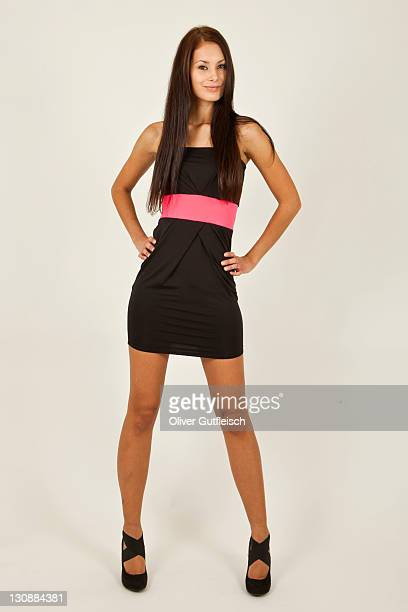 young woman with long brown hair, black dress and high heels posing standing - full frontal woman fotografías e imágenes de stock