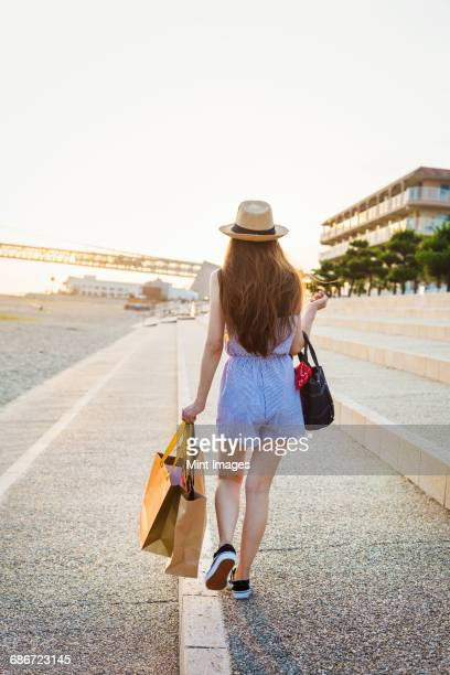 Young woman with long brown hair, wearing Panama hat and carrying shopping bags.