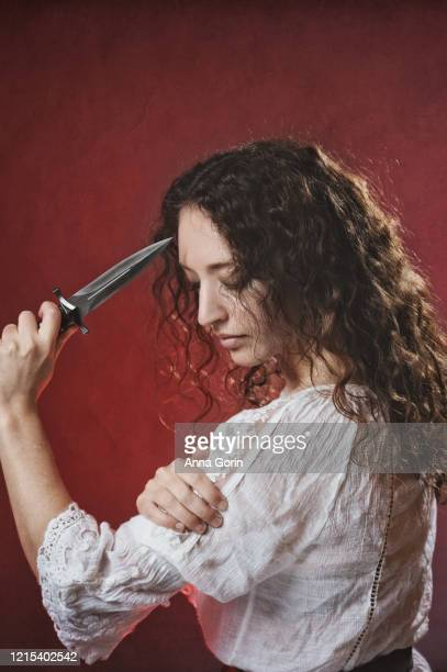 young woman with long curly dark hair wearing white medieval-styled blouse holding dagger to forehead, looking down, studio shot with textured red background - down blouse stock-fotos und bilder