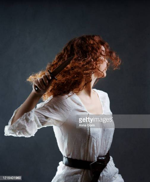 young woman with long curly red hair wearing white medieval-styled blouse and knotted leather belt and holding dagger, turning away from camera, studio shot with textured gray background - turning stock pictures, royalty-free photos & images