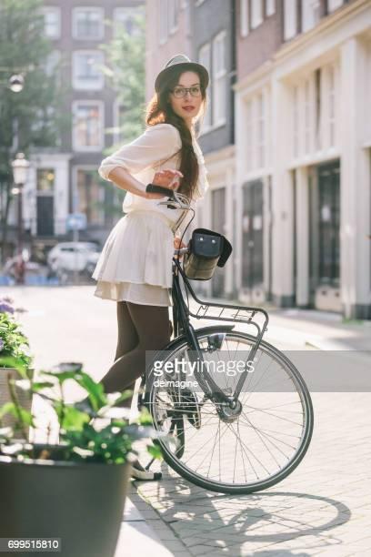Jonge vrouw met lang haar met de fiets in Amsterdam straten