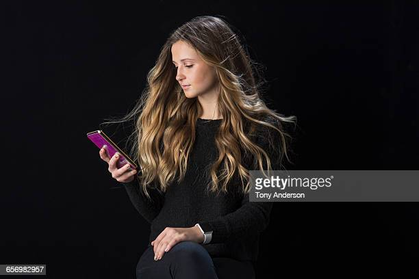 Young woman with long hair checking phone