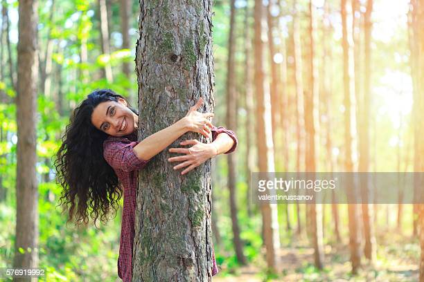 Young woman with long hair embracing tree in the forest