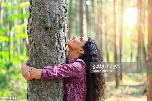 Young woman with long hair hugging tree in the forest