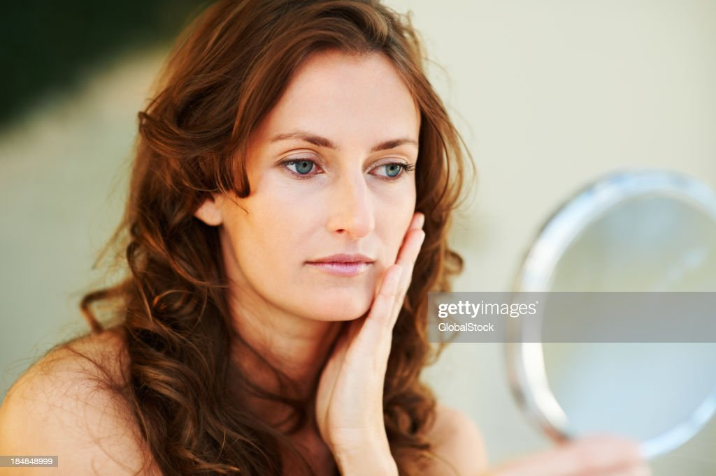 Young woman with long hair looking at reflection in mirror : Stock Photo