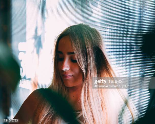 Young Woman With Long Hair Looking Down While Standing Against Window