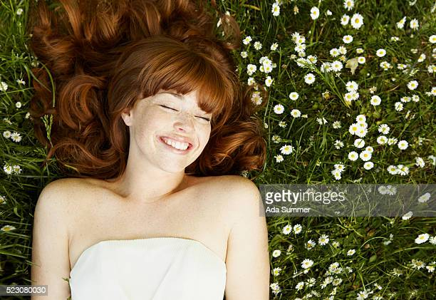 Young woman with long hair, lying in flowers