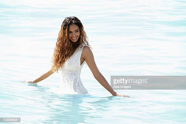 young woman with long hair playing in water - waist deep in water stock pictures, royalty-free photos & images