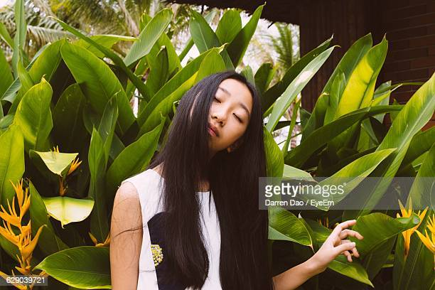 Young Woman With Long Hair Standing Against Plants In Back Yard