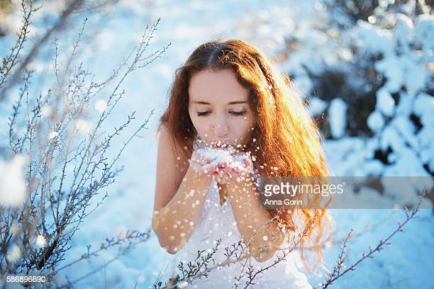 Young woman with long red hair blowing snowflakes from bare hands, wearing sleeveless white dress outdoors in snow