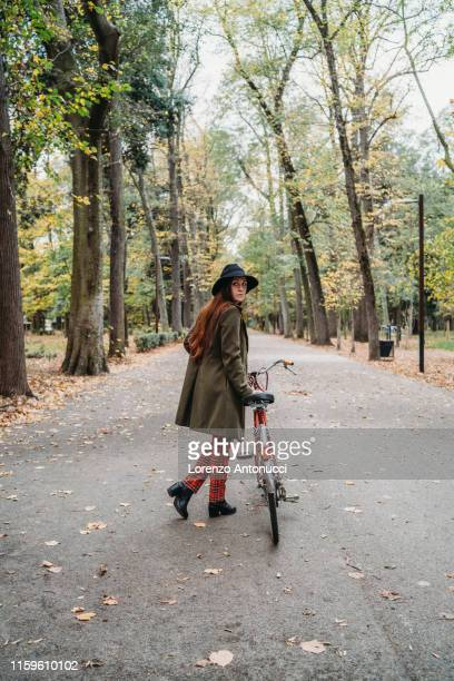 young woman with long red hair looking over her shoulder while pushing bicycle in autumn park, full length, florence, tuscany, italy - pedalantrieb stock-fotos und bilder