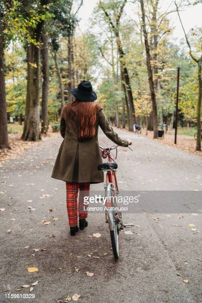 young woman with long red hair pushing bicycle in autumn park, rear view full length, florence, tuscany, italy - coat stock pictures, royalty-free photos & images