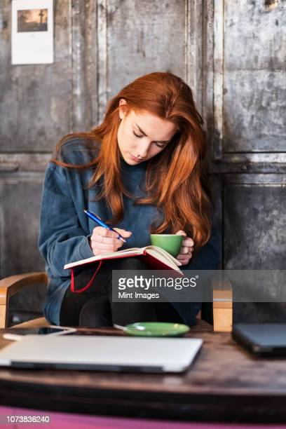 young woman with long red hair sitting at table, holding notebook and cup of coffee. - writing stock pictures, royalty-free photos & images