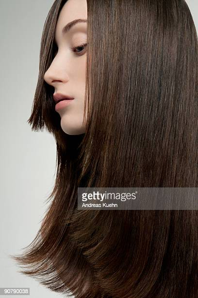 Young woman with long shiny straight hair, profile