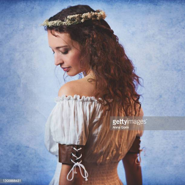 young woman with long wavy red hair wearing off-shoulder peasant blouse and flower crown, looking down at shoulder, studio shot with textured blue backdrop - down blouse stockfoto's en -beelden
