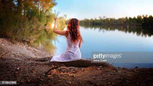 young woman with long wavy red hair wearing sleeveless white dress holds lantern above head, sitting by lake at twilight, rear view - lake auburn stock photos and pictures