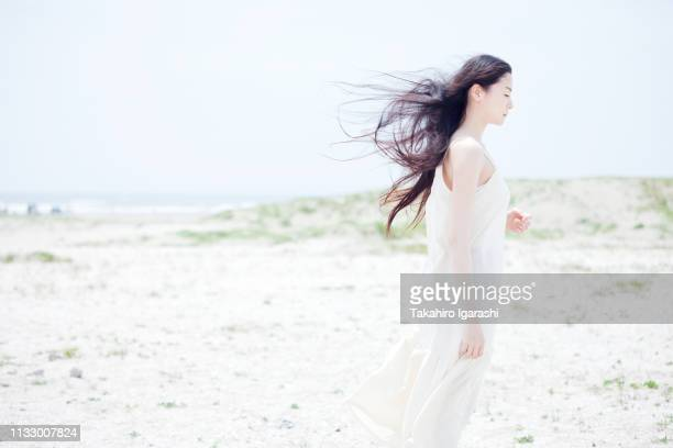 young woman with long windswept black hair on beach - 白い服 ストックフォトと画像