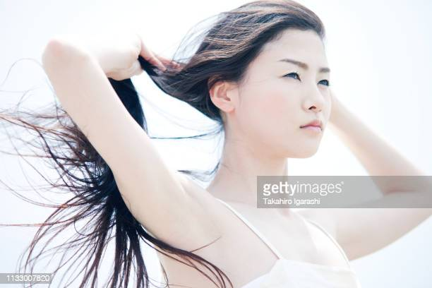 young woman with long windswept black hair - 髪に手をやる ストックフォトと画像