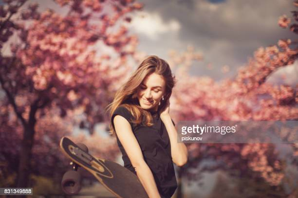 Young woman with longboard in cherry blossom alley